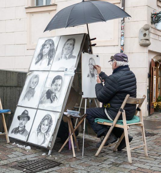 prague-czech-republic-december-2018-a-street-artist-painting-a-portrait-from-the-photograph-on-the_t20_rRxewX